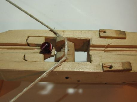Trigger mechanism The piece that holds the string has a gap in the middle.